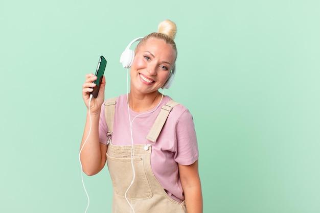 Hübsche blonde frau hört musik mit kopfhörern