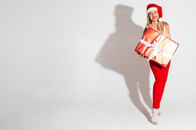 Hübsche blonde frau in der weihnachtsmütze, die lächelt und ein eingewickeltes weihnachtsgeschenk hält. urlaubskonzept. speicherplatz kopieren