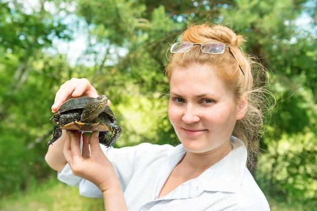 Hübsche blonde frau in gläsern, die eine haustierschildkröte in den händen über grünem sonnigem hintergrund hält