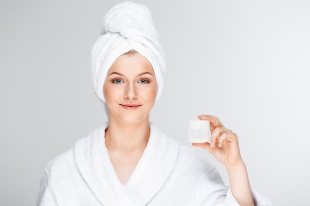 Hübsche blonde frau mit badetuch auf haar, das creme zeigt