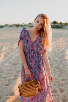 Hübsche blonde frau mit blumenstrauß des lavendels, der auf dem strand geht. sonnenuntergangsfarben.