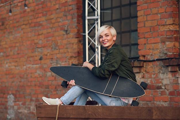 Hübsche blonde frau mit longboard an der mauer.