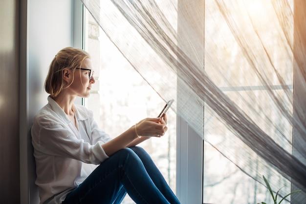 Hübsche blonde frau mit nackten füßen in brille, jeans und weißem hemd, die im sonnenlicht auf der fensterbank sitzt und smartphone in der hand hält. entspannung im gemütlichen wohninterieur. seitenansicht, nahaufnahme.