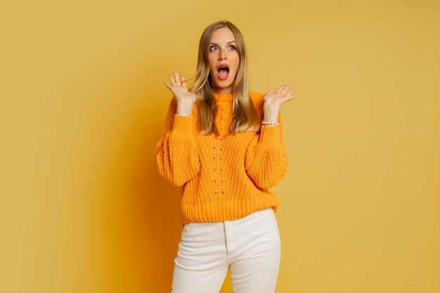 Hübsche blonde frau mit überraschendem gesicht im orange stilvollen herbstpullover, der auf gelb aufwirft.