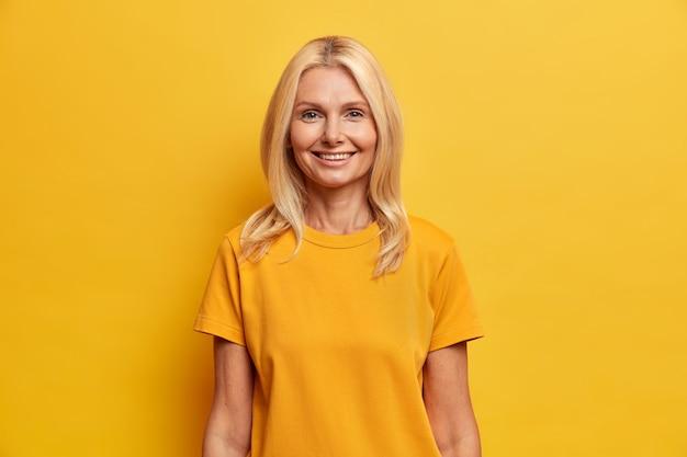 Hübsche blonde frau mittleren alters lächelt sanft gekleidet in freizeitkleidung drückt positive emotionen aus. fröhliche europäische frau genießt angenehmes gespräch