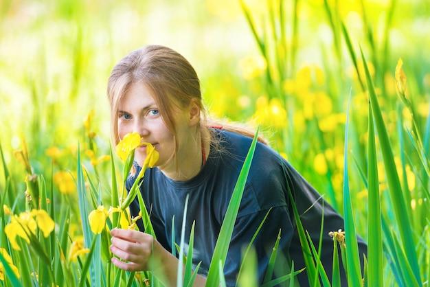 Hübsche blonde frau riecht gelbe blumen auf der sonnigen grünen wiese