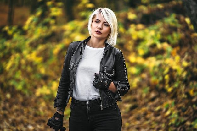Hübsche blonde frauen im bikerstil in schwarzer lederjacke mit sonnenbrille, die draußen im wald steht