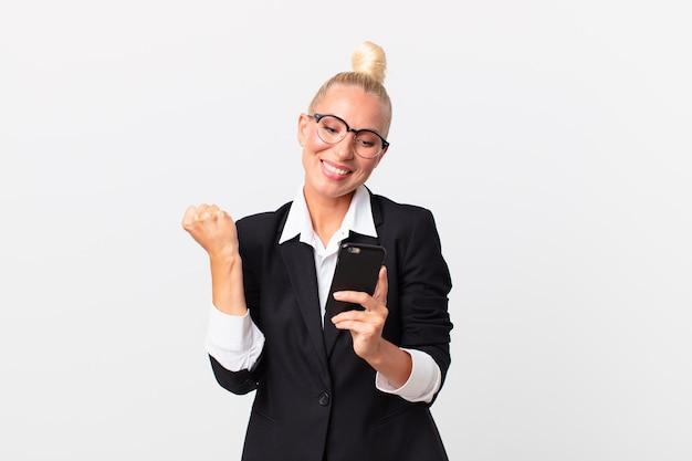 Hübsche blonde geschäftsfrau mit einem smartphone