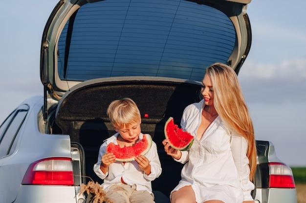 Hübsche blonde haarfrau mit kleinem blondem sohn bei sonnenuntergang, der sich hinter dem auto entspannt und wassermelone isst. sommer, reisen, natur und frische luft auf dem land.