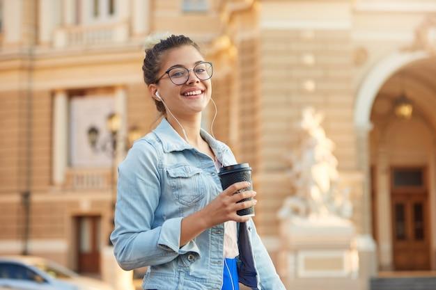 Hübsche blonde junge frau in gläsern geht in einer jeansjacke durch die stadt, trinkt kaffee, hört in kopfhörern lieblingsmusik