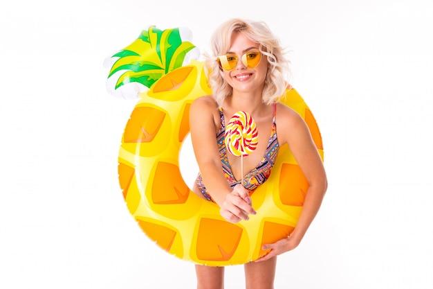 Hübsche blonde kaukasische frau steht im badeanzug mit gummi strand ananas ring und isst einen lolipop isoliert auf weiß