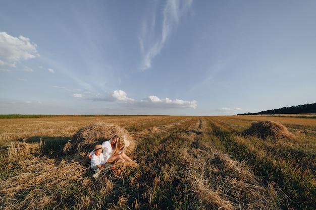 Hübsche blonde langhaarige frau mit dem kleinen blonden sohn bei sonnenuntergang, der sich auf dem feld entspannt und früchte aus einem strohkorb genießt. sommer, landwirtschaft, natur und frische luft auf dem land.