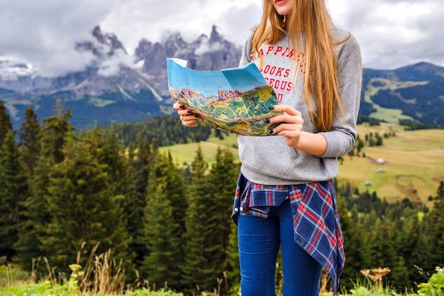 Hübsche blonde reisende frau an den bergen, die eine karte halten. abenteuer, alleine reisen