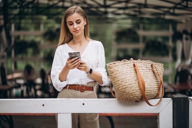 Hübsche blondine, die draußen telefon im park verwenden