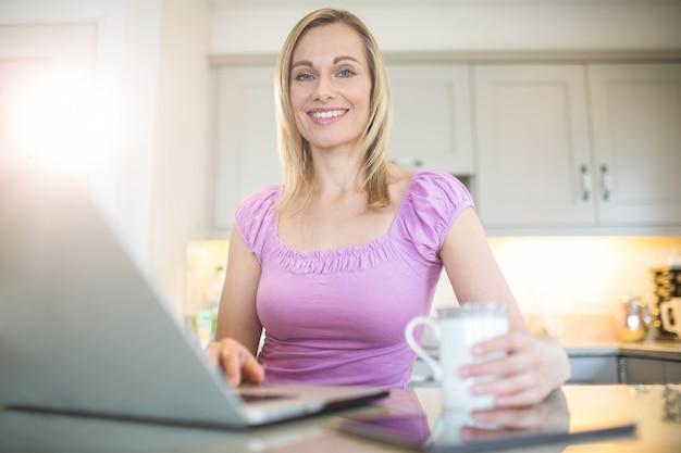 Hübsche blondine, die kaffee trinken und laptop verwenden