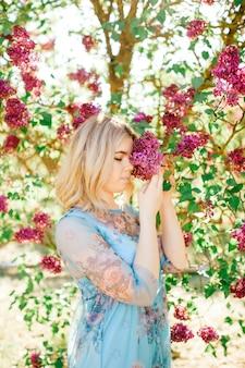 Hübsche blondine im schönen blauen kleid, das in blühenden büschen aufwirft.