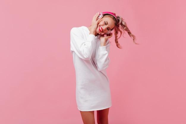 Hübsche blondine im sportoutfit, die musik in rosa kopfhörern hört