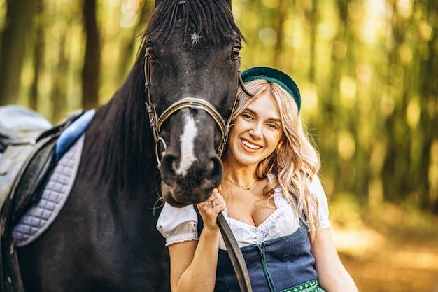 Hübsche blondine in traditioneller kleidung, die mit großem schwarzen pferd im wald geht