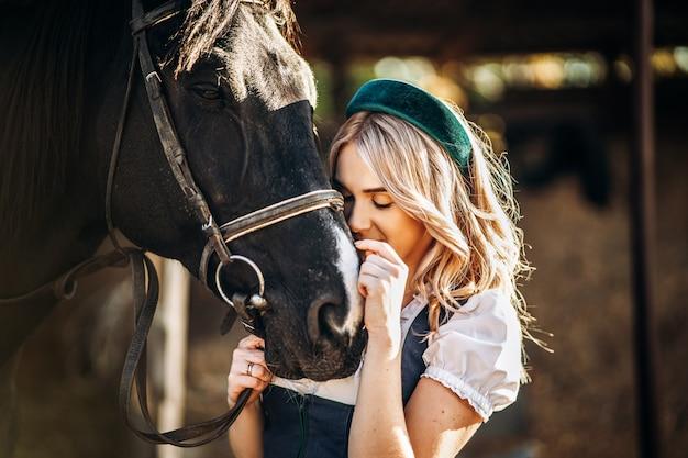 Hübsche blondine in traditioneller kleidung kümmert sich auf der farm um das große schwarze pferd