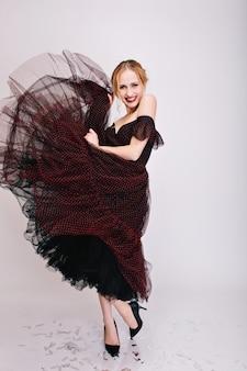 Hübsche blondine tanzt mit überfallkleid, hat spaß, genießt party, lächelt. trägt elegante schwarze schuhe mit absätzen, schwarzes kleid mit flauschigem rock.