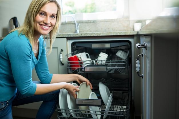 Hübsche blondine, welche die spülmaschine leeren