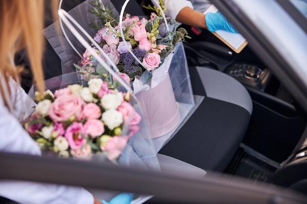 Hübsche blumensträuße werden in einem auto geliefert