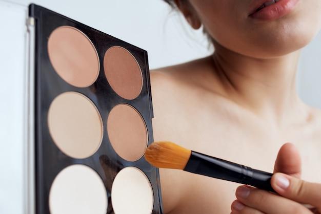 Hübsche brünette, die make-up auf der gesichtspflege aufträgt. foto in hoher qualität