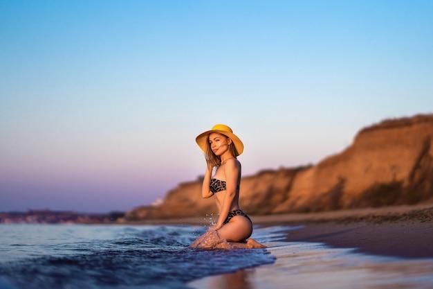 Hübsche brünette frau, die am strand am meer entspannt.