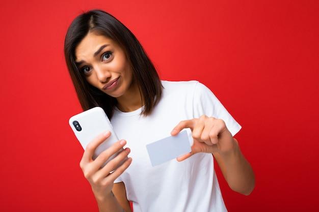 Hübsche brünette frau, die jeden tag ein stilvolles weißes t-shirt trägt, isoliert auf rotem hintergrund, das telefon und kreditkarte hält und mit der zahlung in die kamera schaut und fragen hat