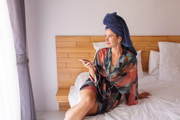 Hübsche brünette frau eingewickelt in ein duschtuch unter verwendung des mobiltelefons beim sitzen auf dem bett