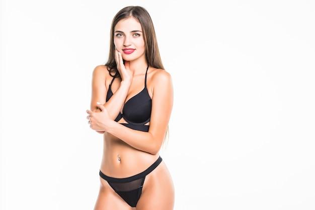 Hübsche brünette frau im schwarzen badeanzug, der auf weißer wand aufwirft