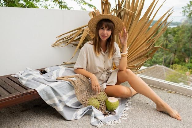 Hübsche brünette frau im strohhut und im leinenkleid, die auf terrasse über trockenem palmblatt aufwirft. frische kokosnüsse.