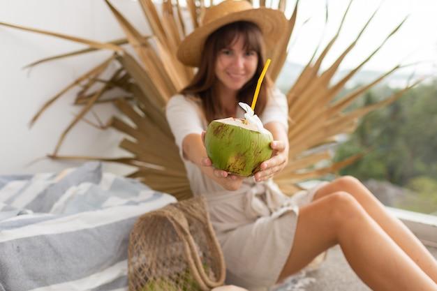 Hübsche brünette frau im strohhut und im leinenkleid, die auf terrasse über trockenem palmblatt, das frische kokosnuss hält, aufwirft.