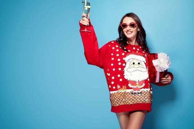 Hübsche brünette frau in der sonnenbrille und im roten pullover mit santa design mit geschenkbox