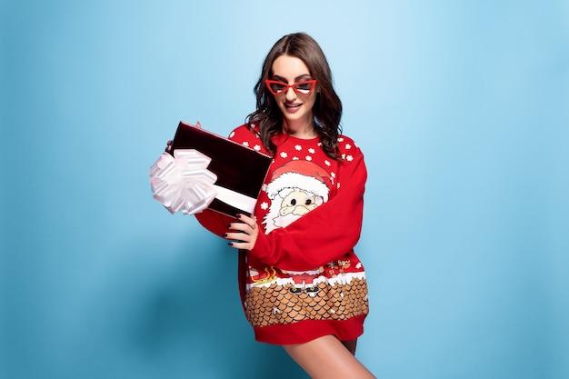 Hübsche brünette frau in der sonnenbrille und im roten übergroßen pullover mit santa design mit geschenkbox