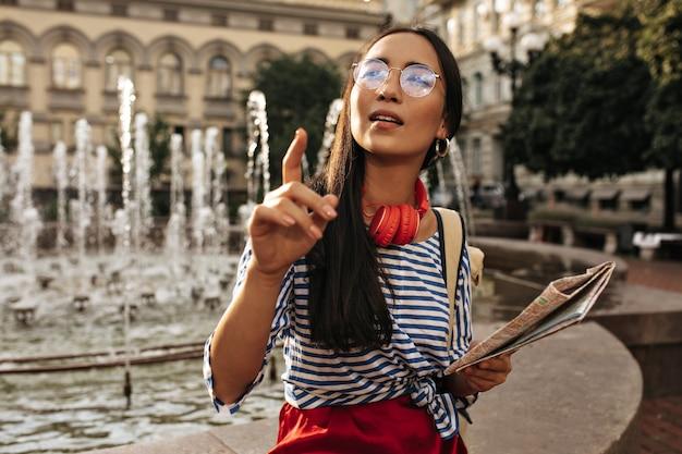 Hübsche brünette frau in stylischem gestreiftem hemd, roten kopfhörern und seidenrock zeigt in die ferne