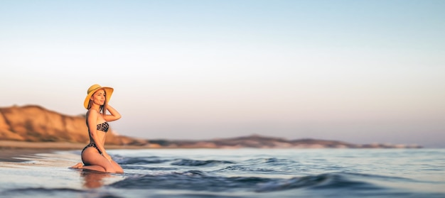 Hübsche brünette frau mit hut, die sich hinsetzt und am strand posiert