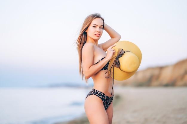 Hübsche brünette frau mit hut posiert am strand