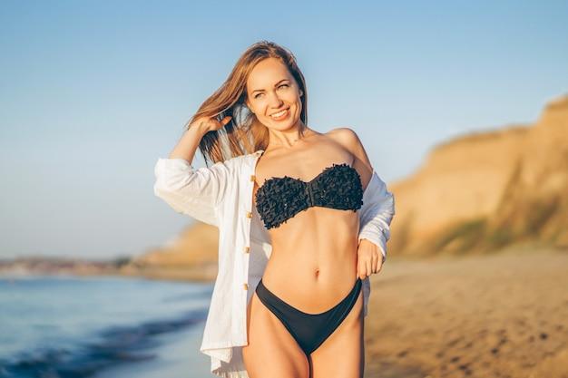 Hübsche brünette frau mit weißem hemd posiert am strand
