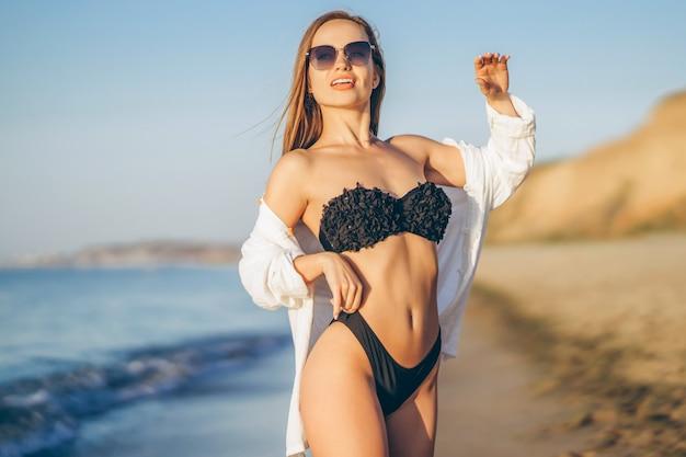 Hübsche brünette frau mit weißem hemd und sonnenbrille posiert am strand