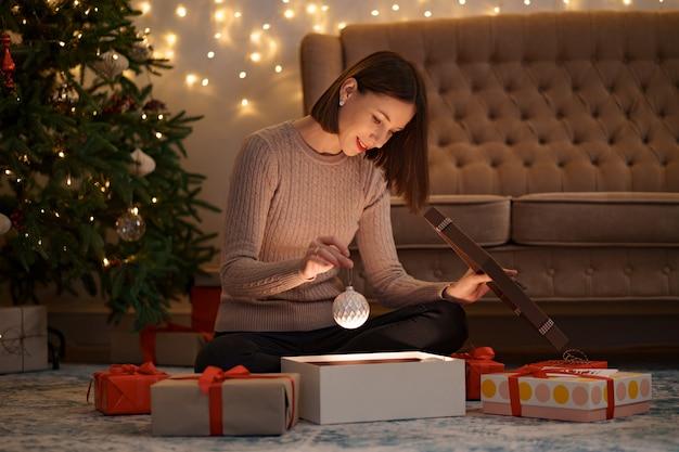 Hübsche brünette frau öffnet ein entzückendes geschenk, das eine weiße weihnachtskugel hält