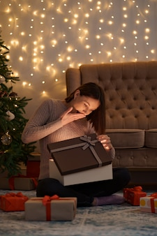 Hübsche brünette frau öffnet ein entzückendes geschenk mit lichtern