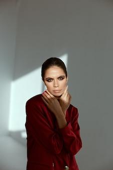 Hübsche brünette helle make-up hände nahe gesicht rote jacke mode glamour