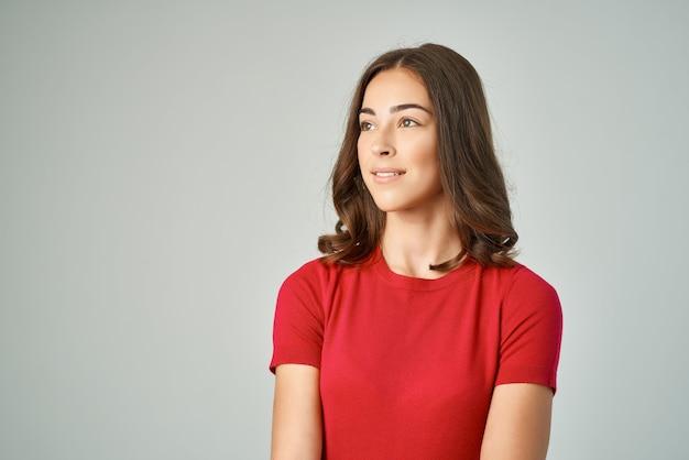 Hübsche brünette im roten t-shirt abgeschnittenes lächeln isolierter hintergrund
