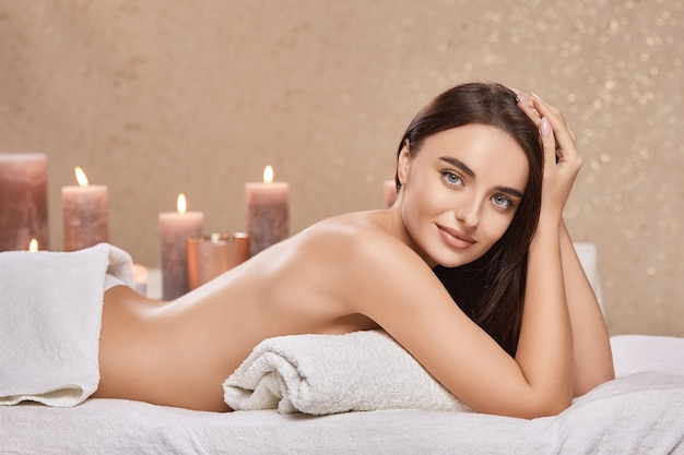 Hübsche brünette im spa mit weißen handtüchern und nacktem rücken