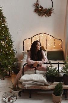 Hübsche brünette junge frau im gemütlichen pyjama, die auf dem bett neben dem weihnachtsbaum sitzt.