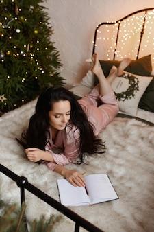 Hübsche brünette junge frau in gemütlicher nachtwäsche, die auf dem bett sitzt und neujahrspläne im notizbuch neben dem weihnachtsbaum schreibt.