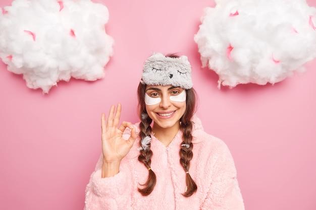 Hübsche brünette kaukasische frau lächelt sanft zeigt okay geste mag etwas trägt kollagenpflaster auf, um schwellungen unter den augen zu reduzieren, gekleidet in weicher nachtwäsche, isoliert über rosa wand