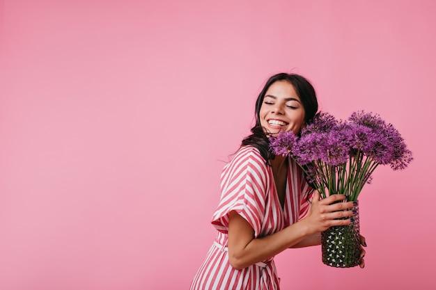 Hübsche brünette lächelt blendend, während sie präsentierte blumen genießt. porträt des mädchens im rosa gestreiften oberteil, das ihre augen vor glück schließt.