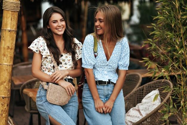 Hübsche brünette, lockige frau in weißer blumenbluse und jeans und ihre attraktive blonde freundin in blauem oberteil und jeanshose reden und lehnen sich auf holztisch im straßencafé